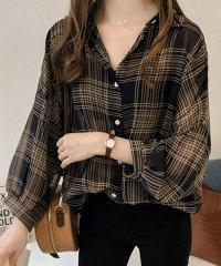 短めの長袖とゆったりしたシルエットが女性らしいチェックシャツ。